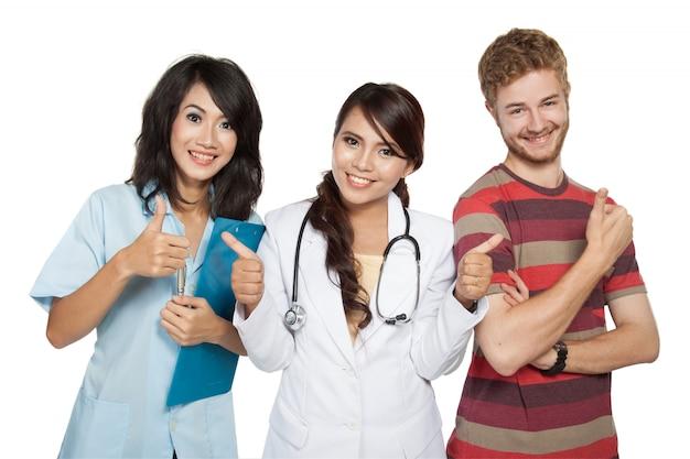 Ärztin mit assistentin und patientin, die daumen aufgibt