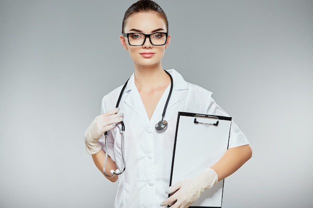 Ärztin mit braunen haaren und nacktem make-up trägt weiße medizinische uniform, brille, stethoskope und weiße handschuhe am grauen studiohintergrund und hält notizen.