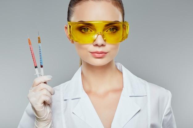 Ärztin mit braunen haaren und nacktem make-up trägt weiße medizinische uniform, brille, stethoskope und weiße handschuhe am grauen studiohintergrund und hält spritzen, nahaufnahme.