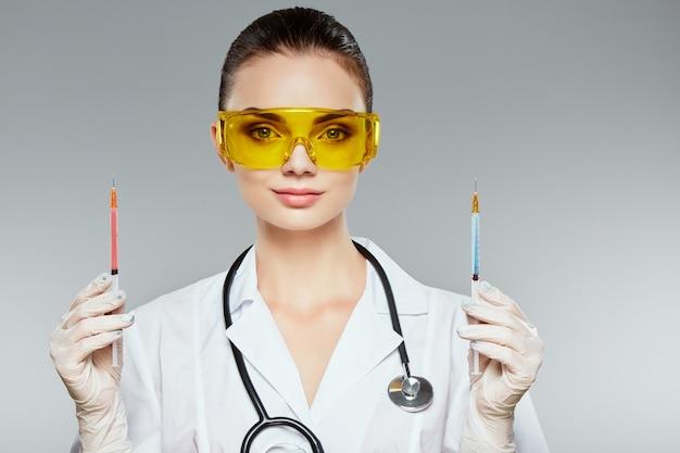 Ärztin mit braunen haaren und nacktem make-up trägt weiße medizinische uniform, brille, stethoskope und weiße handschuhe am grauen studiohintergrund und hält spritzen.