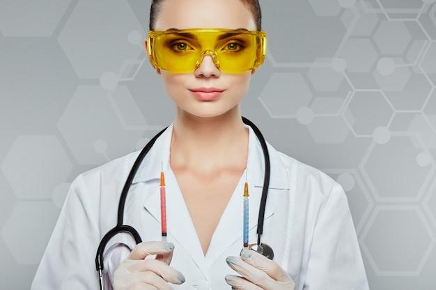 Ärztin mit braunen haaren und nacktem make-up trägt weiße medizinische uniform, gelbe schutzbrille, stethoskop und hält zwei spritzen am grauen studiohintergrund