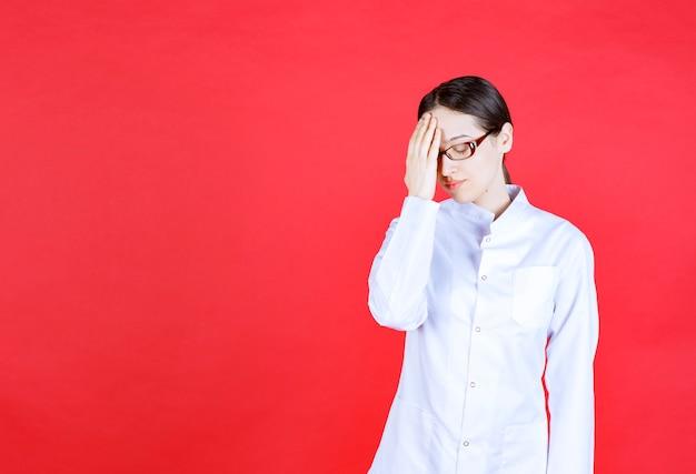 Ärztin mit brille, die auf rotem hintergrund steht und den kopf mit den händen hält und erschrocken aussieht.