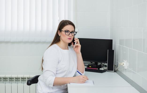 Ärztin mit brille und weißem mantel sitzt an ihrem schreibtisch und telefoniert