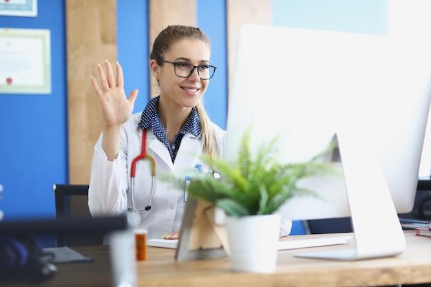 Ärztin mit brille winkt mit der hand am laptop-bildschirm in der klinik
