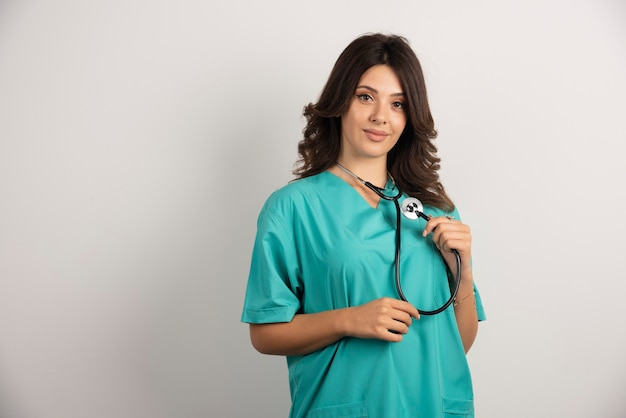 Ärztin mit dem stethoskop, das auf weiß aufwirft.