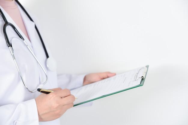 Ärztin mit dem stethoskop, das ein klemmbrett für krankenblätter hält.