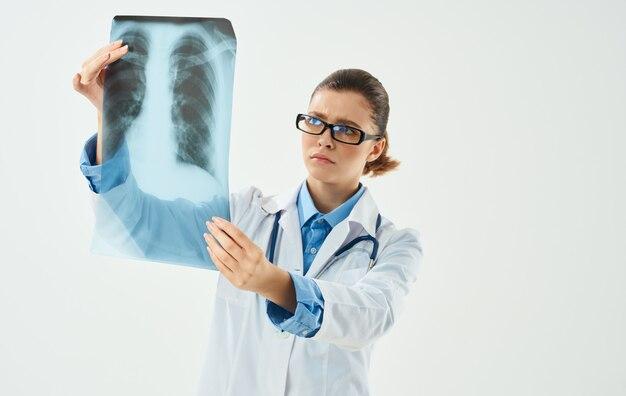Ärztin mit einer röntgenaufnahme auf einem licht und einem medizinischen kleid emotionen modell.