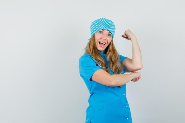 Ärztin mit erhobener faust in blauer uniform und fröhlich aussehend