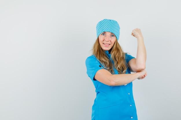 Ärztin mit geballter faust in blauer uniform und fröhlich aussehend.