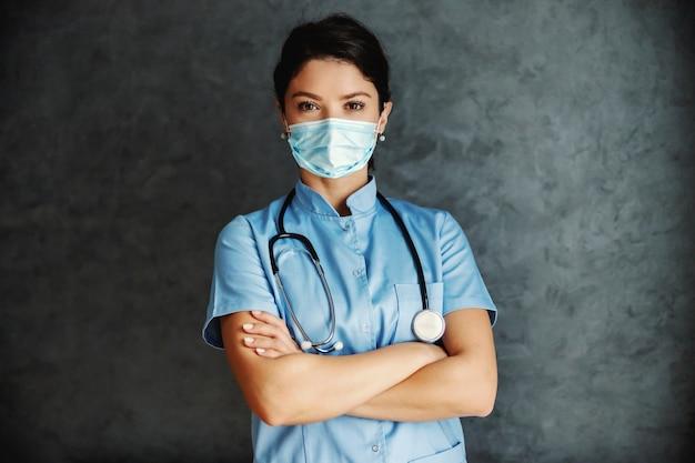 Ärztin mit gesichtsmaske, die mit verschränkten armen steht und kamera betrachtet. sie ist bereit, leben zu retten.