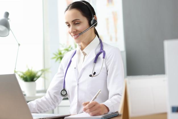 Ärztin mit headset, das in laptop-bildschirm schaut. psychologische hilfe online-konzept