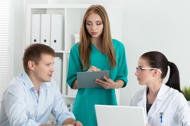 Ärztin mit ihrem kollegen, der männliche patientin berät. gesundheits- und medizinkonzept.