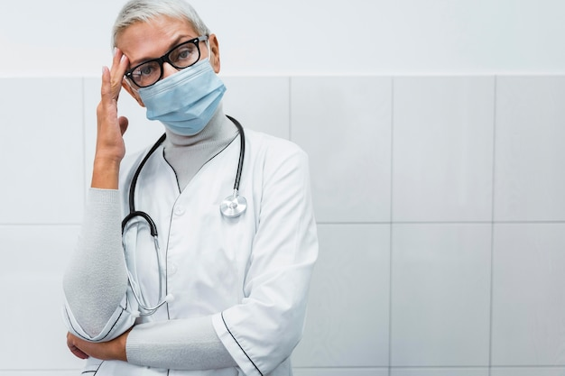 Ärztin mit kopfschmerzen mit kopierraum