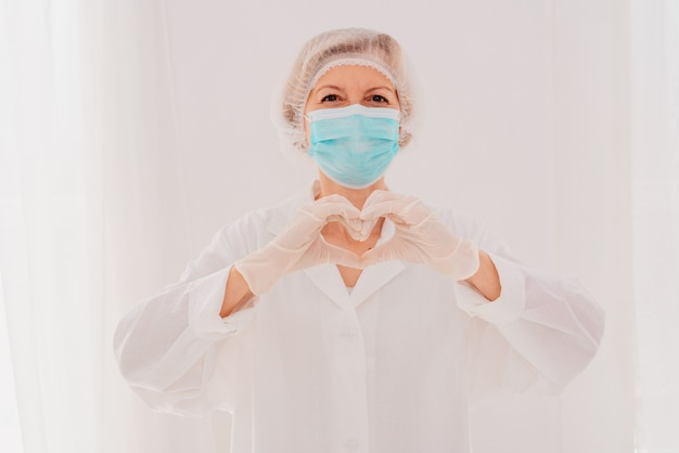 Ärztin mit maske macht mit ihren händen ein herz