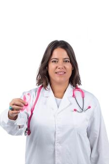 Ärztin mit rosa stethoskop, das rosa band des brustkrebses auf einem weißen hintergrund hält.