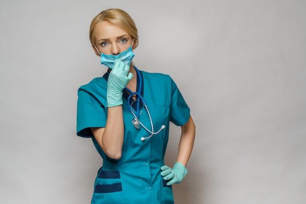 Ärztin mit schutzmaske und gummi- oder latexhandschuhen - müde und gestresst