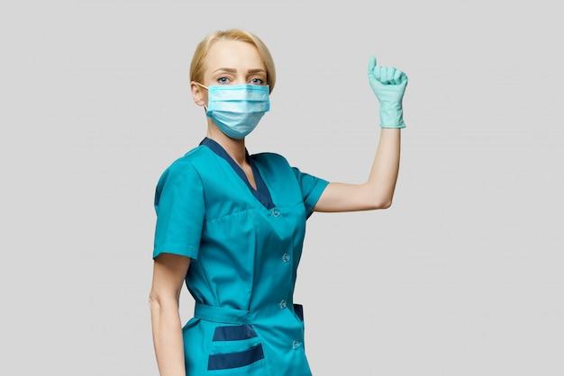 Ärztin mit schutzmaske und latexhandschuhen gewinnen ja geste