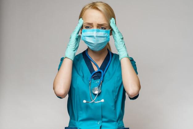 Ärztin mit schutzmaske und latexhandschuhen kopfschmerzen und stress
