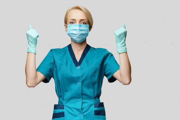 Ärztin mit schutzmaske und latexhandschuhen mit win-geste