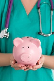 Ärztin mit sparschwein. die hände des doktors in nahaufnahme. krankenversicherung und gesundheitskonzept.