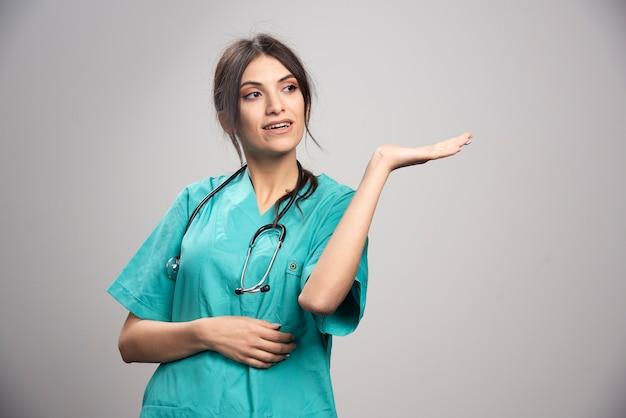 Ärztin mit stethoskop, das auf grau aufwirft