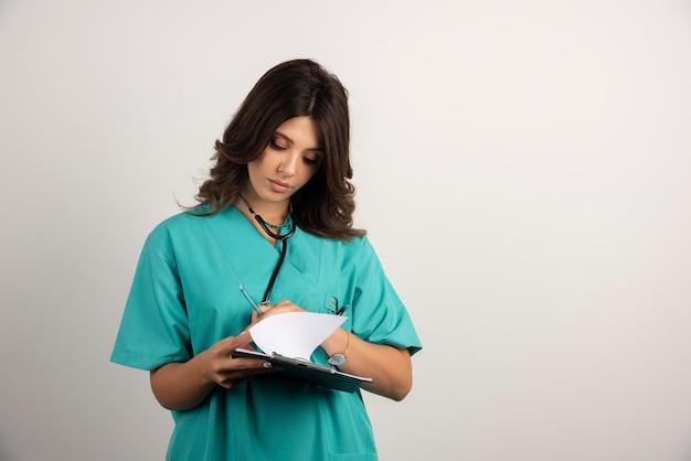 Ärztin mit stethoskop, das notizen aus der zwischenablage liest.