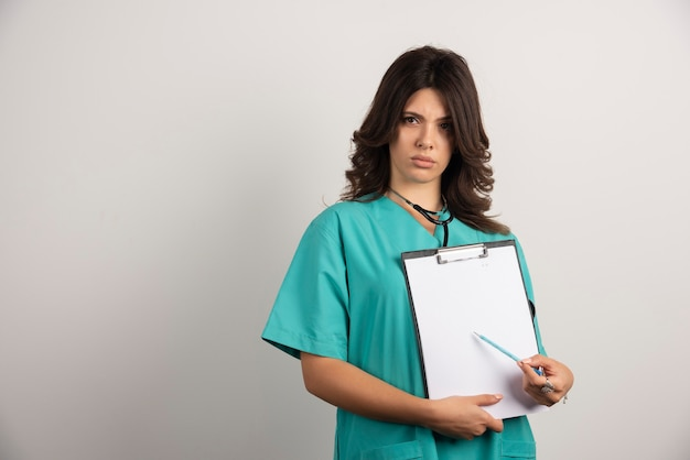 Ärztin mit stethoskop, die sich sorgen macht und ergebnisse zeigt.