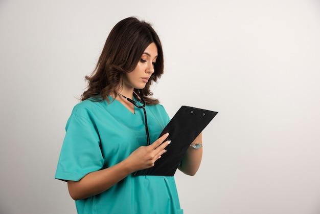Ärztin mit stethoskop, die sorgfältig die papiere liest.