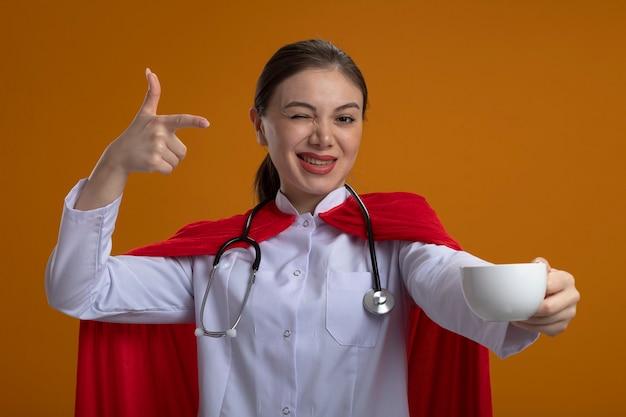 Ärztin mit stethoskop in weißer medizinischer uniform und rotem superheldenumhang, der kaffeetasse zeigt, die mit dem finger darauf zeigt lächelnd und zwinkernd über orange wand steht