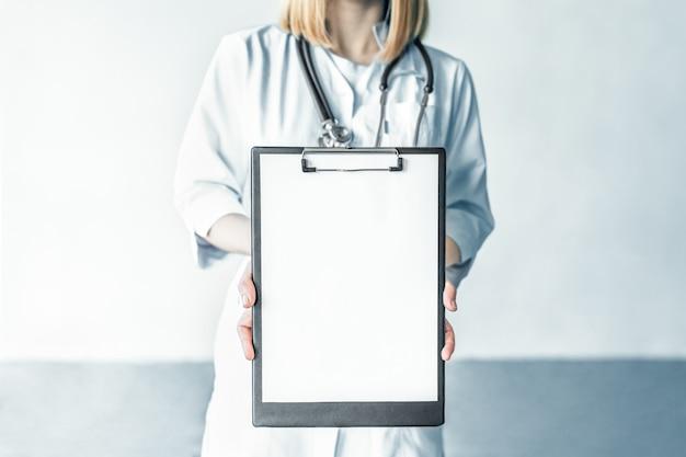 Ärztin mit stethoskop mit zwischenablage auf weißem hintergrund