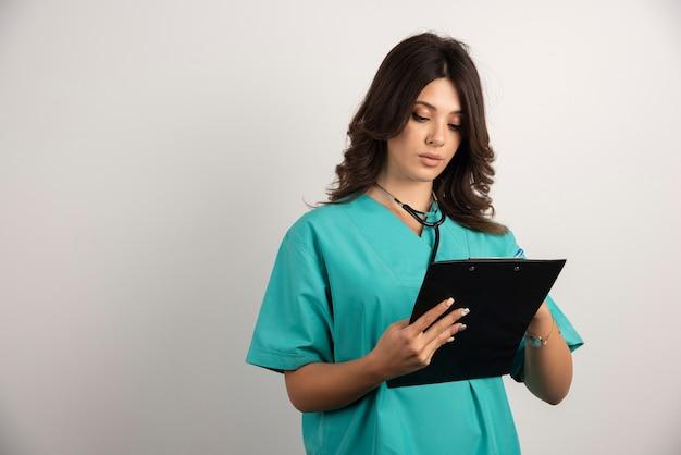 Ärztin mit stethoskop sorgfältig in zwischenablage schreiben.