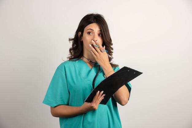 Ärztin mit stethoskop überrascht nach dem lesen der papiere.