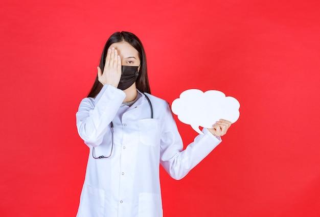 Ärztin mit stethoskop und in schwarzer maske, die einen leeren info-schreibtisch der wolkenform hält und kopf hält.