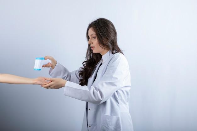 Ärztin mit thermometer, die jemandes temperatur prüft.