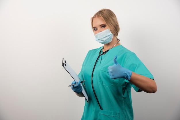 Ärztin mit zwischenablage, die sich daumen zeigt.