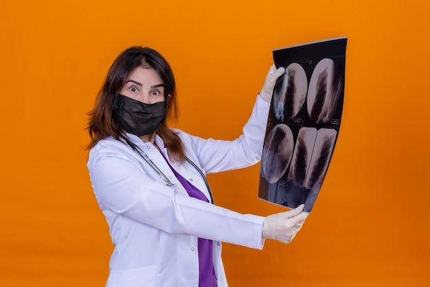 Ärztin mittleren alters, die einen weißen kittel in einer schwarzen gesichtsschutzmaske trägt und mit einem stethoskop, das eine röntgenaufnahme der lunge hält, erstaunt und überrascht ist, wenn sie die kamera betrachtet, die über dem isolierten orangefarbenen rücken steht