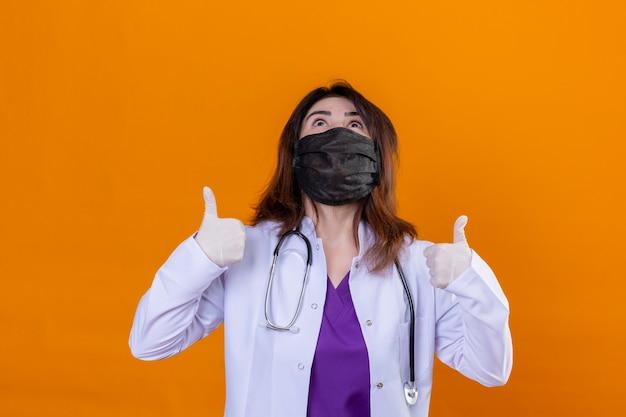 Ärztin mittleren alters, die einen weißen kittel in einer schwarzen gesichtsschutzmaske trägt und mit stethoskop erstaunt und überrascht nach oben schaut und mit fingern und erhobenen armen zeigt, die isoliert stehen
