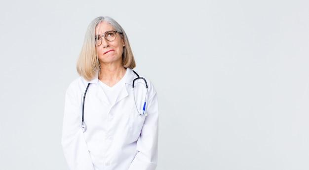 Ärztin mittleren alters, die verwirrt und verwirrt aussieht, sich wundert oder versucht, ein problem zu lösen oder zu denken