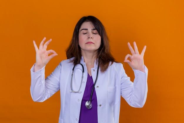 Ärztin mittleren alters, die weißen kittel trägt und mit stethoskop sich entspannt und mit geschlossenen augen lächelt, die meditationsgeste mit den fingern über orangeem hintergrund tun