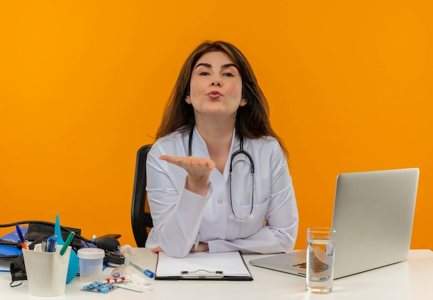 Ärztin mittleren alters im medizinischen gewand mit stethoskop, das am schreibtisch sitzt, arbeiten am laptop mit medizinischen werkzeugen, die kussgeste auf isolierter orange wand mit kopienraum zeigen