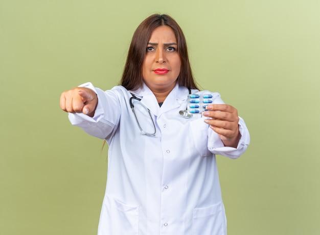 Ärztin mittleren alters im weißen kittel mit stethoskop, das blister mit pillen hält, die mit dem zeigefinger zeigen, der unzufrieden auf grün steht
