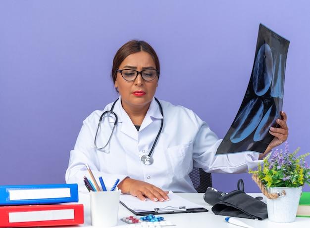 Ärztin mittleren alters im weißen kittel mit stethoskop, das ein röntgenbild hält und die zwischenablage auf dem tisch mit ernstem gesicht am tisch über der blauen wand betrachtet