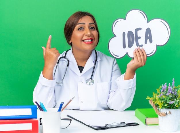 Ärztin mittleren alters im weißen kittel mit stethoskop, das ein sprechblasenschild mit wortidee hält, das lächelt und den zeigefinger zeigt, der am tisch auf grün sitzt