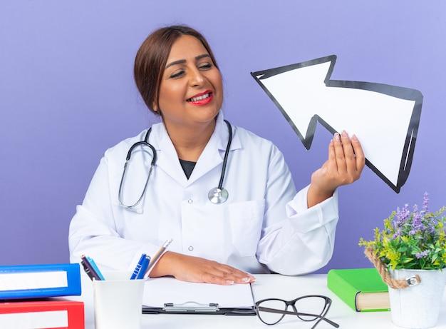 Ärztin mittleren alters im weißen kittel mit stethoskop, das weiß hält und es mit einem lächeln auf einem intelligenten gesicht betrachtet, das am tisch auf blau sitzt