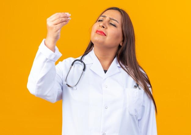 Ärztin mittleren alters im weißen kittel mit stethoskop, die auf ihre finger schaut und geldgeste macht