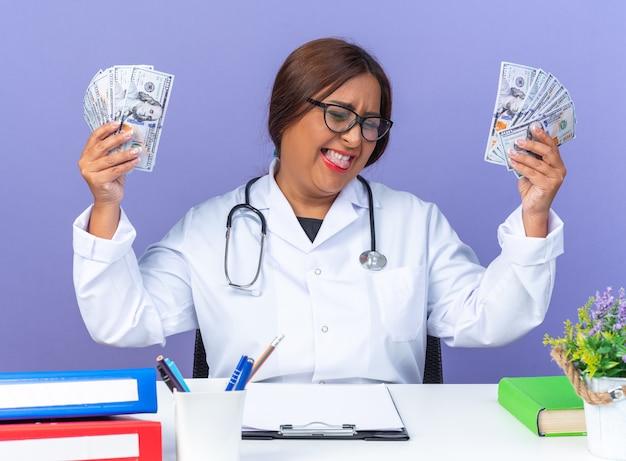 Ärztin mittleren alters im weißen kittel mit stethoskop, die bargeld glücklich und aufgeregt hält und sich über ihren erfolg freut, der am tisch über blauem hintergrund sitzt