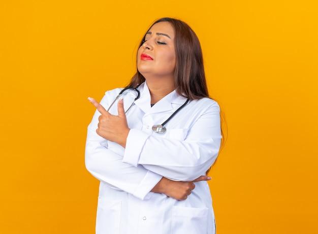 Ärztin mittleren alters im weißen kittel mit stethoskop, die beiseite schaut, mit ernstem, selbstbewusstem ausdruck, der mit dem zeigefinger auf die seite zeigt, die über der orangefarbenen wand steht