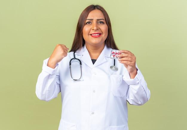 Ärztin mittleren alters im weißen kittel mit stethoskop, die blase mit pillen hält, die die faust zusammenballt und selbstbewusst stehend auf grün lächelt