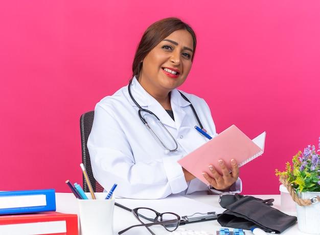 Ärztin mittleren alters im weißen kittel mit stethoskop, die ein notizbuch hält und etwas mit einem lächeln auf ein glückliches gesicht schreibt, das am tisch mit büroordnern auf rosa sitzt