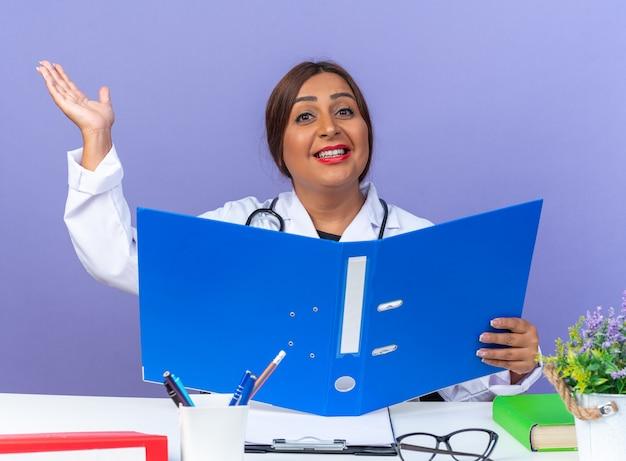 Ärztin mittleren alters im weißen kittel mit stethoskop, die einen büroordner hält und nach vorne schaut, glücklich und positiv, der arm lächelt fröhlich am tisch über blauer wand sitzend